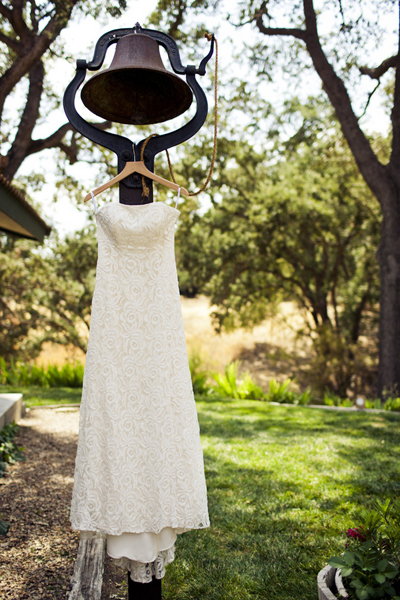 lace wedding dress hanging from bell