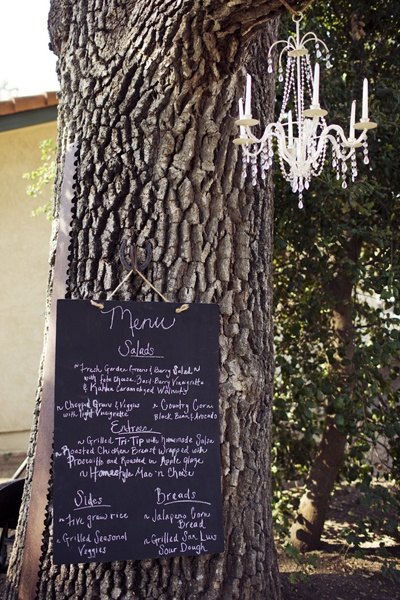 chalkboard wedding menu and chandelier hanging from tree