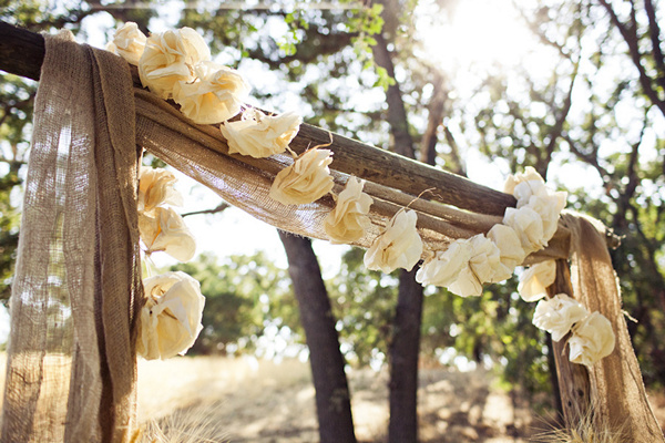 burlap draped wedding altar with fabric flower garland