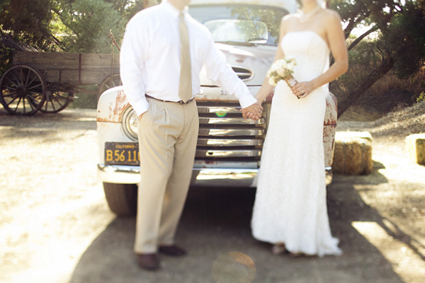 bride and groom holding hands in front of vintage pick-up truck