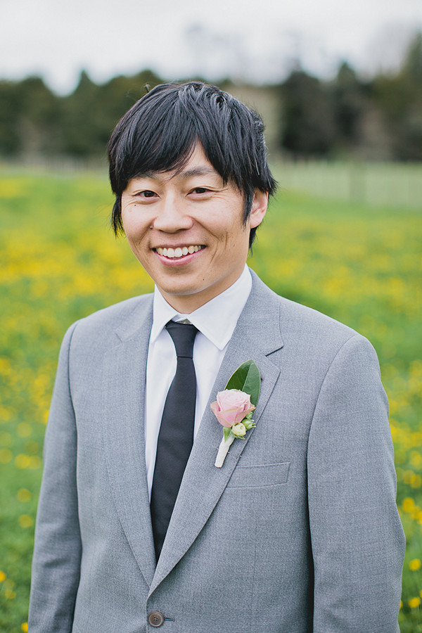 groom in grey suit and pink rose boutonniere