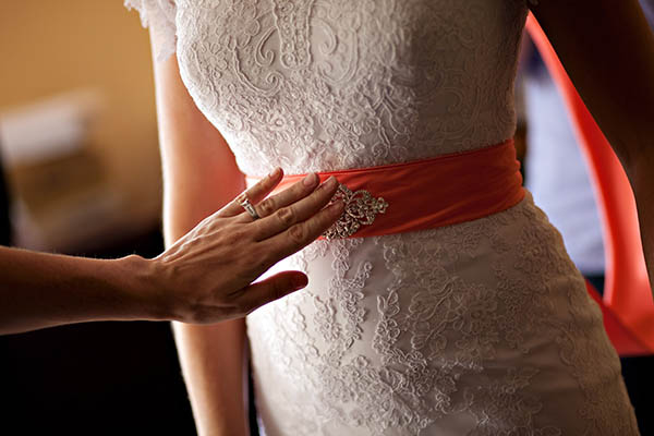 lace wedding dress with coral sash