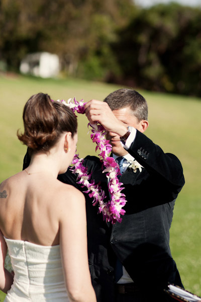 groom putting lei on bride
