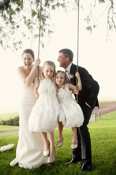 bride and groom with flower girls on tree swing
