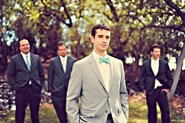 groom in grey suit and aqua bow tie