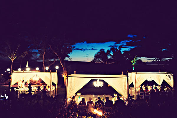 outdoor Hawaii wedding reception lit with chandeliers