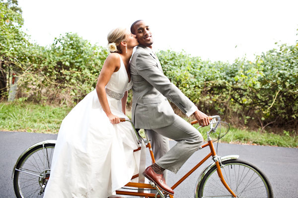 bride and groom riding tandem bicycle