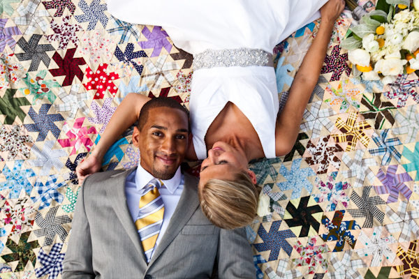 bride and groom lying on quilt