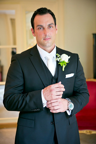 groom in black suit and white tie
