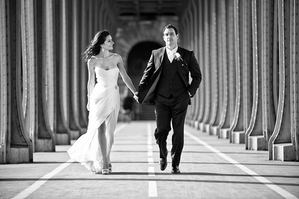 bride and groom walking on Paris bridge