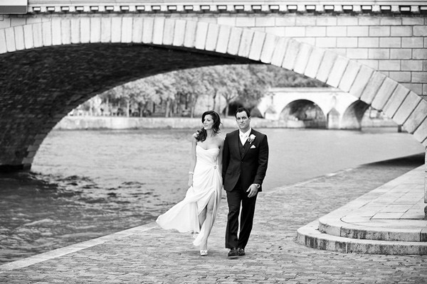 bride and groom walking by the seine