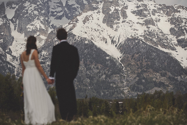 bride and groom looking at the mountains