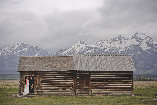 bride and groom in doorway of log cabin