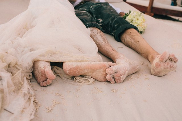 bride and groom covered in sand