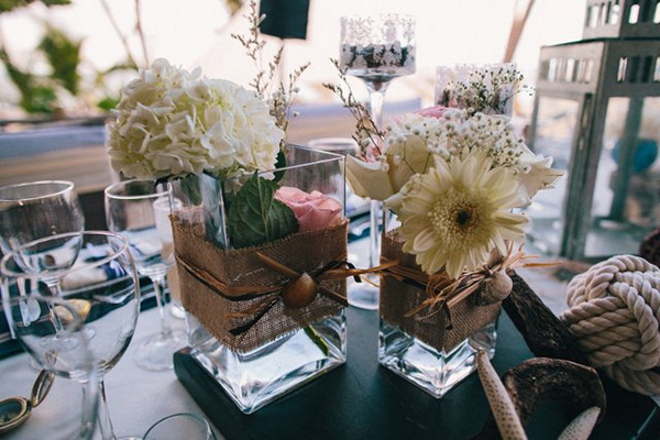 white flower arrangements in burlap wrapped vases