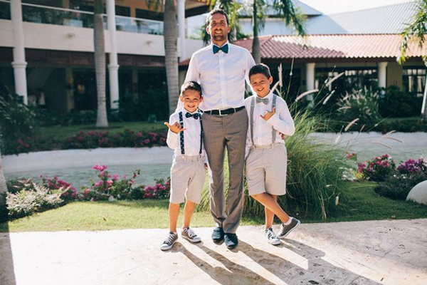 Groom in teal bow tie with young groomsmen