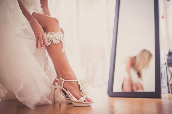bride putting on lace garter