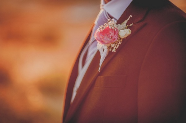 groom with pink rose boutonniere