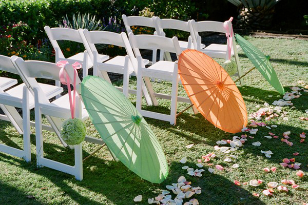 outdoor wedding aisle with green and orange parasols