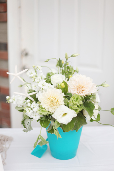 beach wedding flower arrangement in sand pail