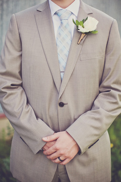 groom in tan suit with white rose boutonniere