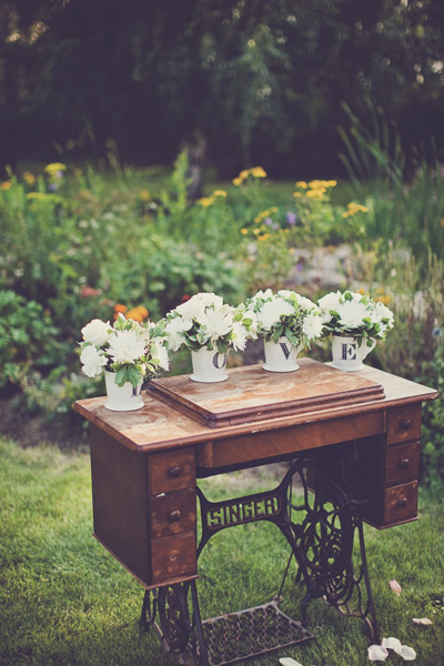 vintage sewing machine wedding table with LOVE mug flower arrangements