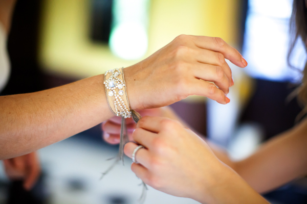 bride tying on bracelet