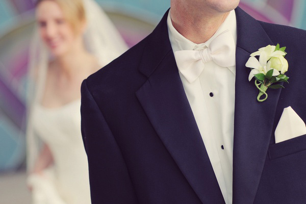 groom in tuxedo with white bow tie