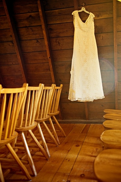 lace wedding dress hanging in barn