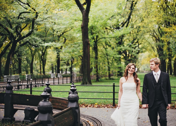 bride and groom walking through central park