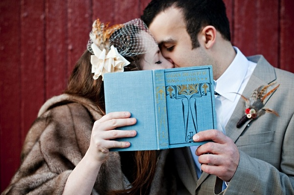 bride and groom kissing behind vintage book
