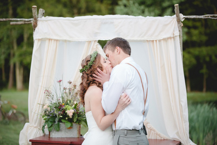bride and groom first kiss on tree farm