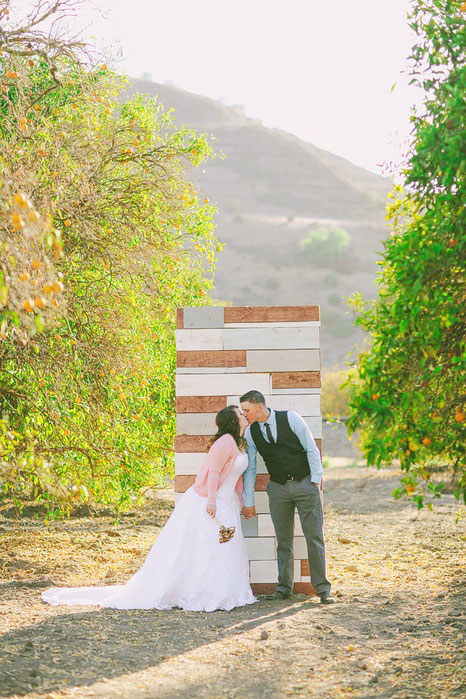 bride and groom kissing in front of ceremony backdrop