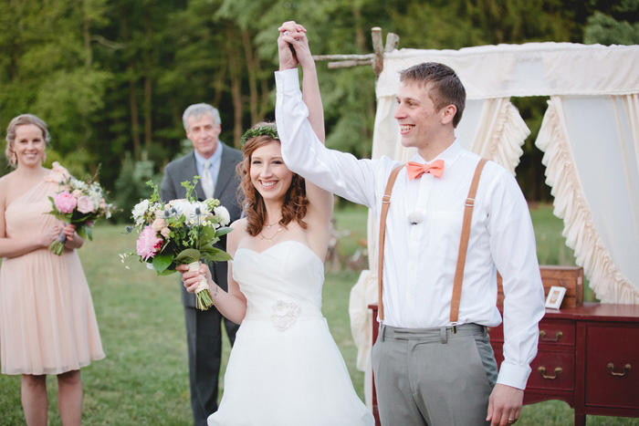 bride and groom with arms raised in victory
