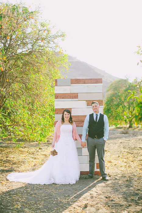 bride and groom in front of wooden ceremomy back drop