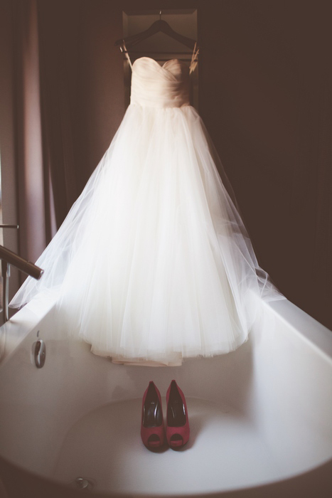 tulle wedding dress hanging in bathtub