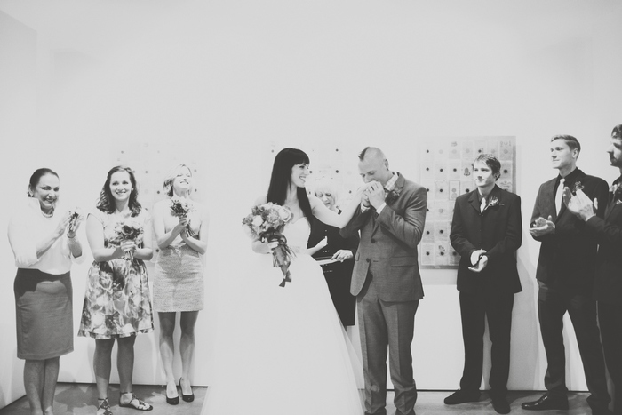 groom kissing bride's hand