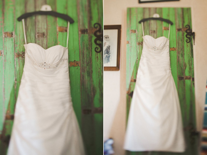 wedding dress hanging on green door