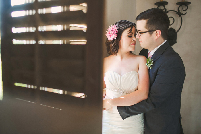 bride and groom portrait behind wooden shutter