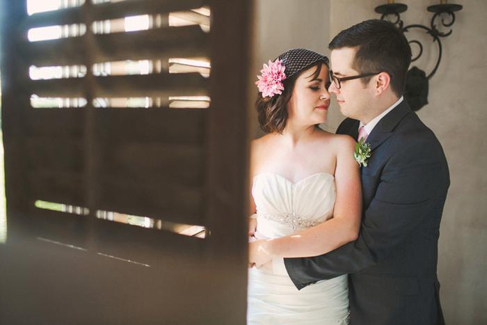 bride and groom portrait behind wooden shutter