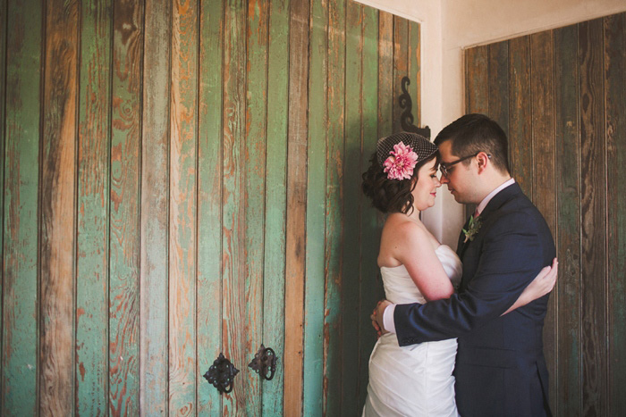 bride and groom portrait in front of green wooden door