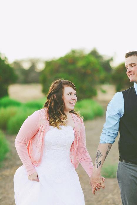 bride and groom walking through orange grove