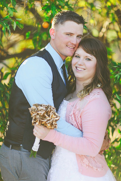 bride in pink cardigan with gold rose bouquet