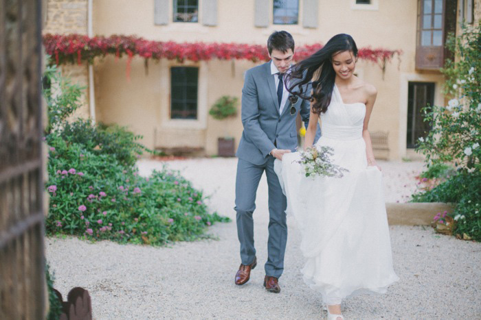 groom helping bride with her dress