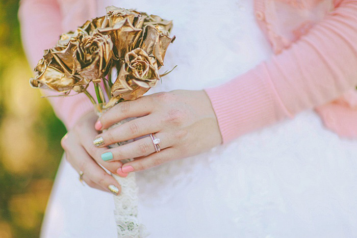 bride with pastel nails and gold rose bouquet
