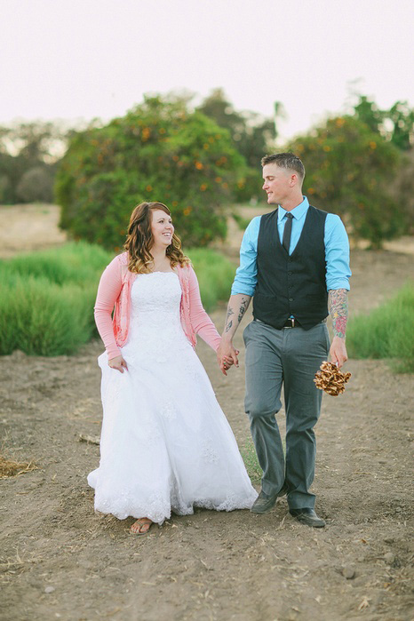 bride and groom walking in orange grove