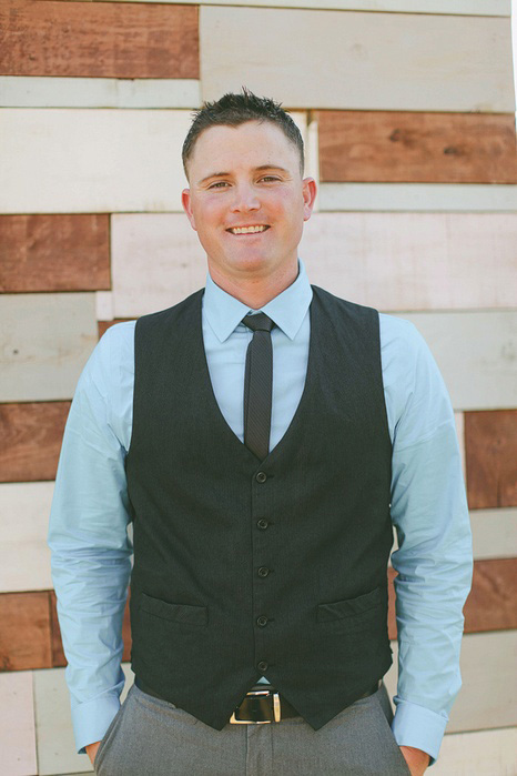 groom in blue shirt and black vest