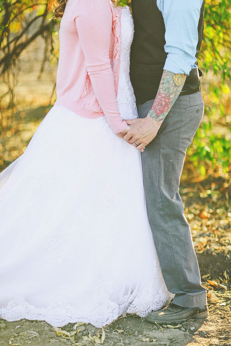 bride with pink cardigan and groom with arm tattoos