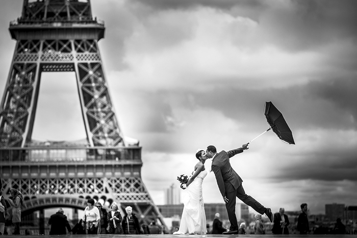 bride and groom with umbrella in front of eiffel tower