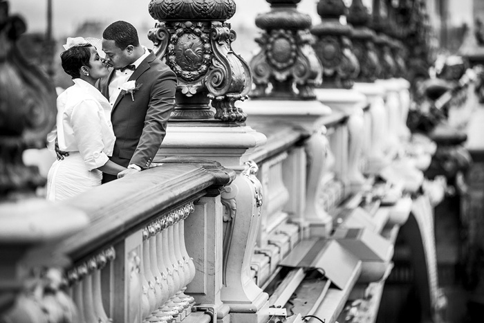 bride and groom kissing on bridge in Paris